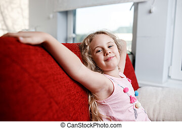 Happy 6 year old girl is sitting on red chair in his room.