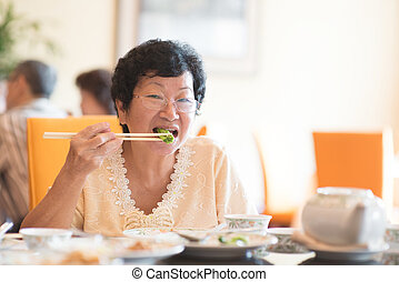 Senior Asian Woman eating vegetable - Happy 60s Senior Asian...