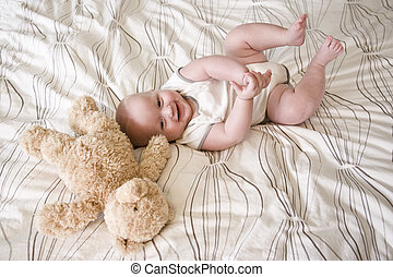 Happy 7 month old baby lying down by teddy bear - Happy 7...