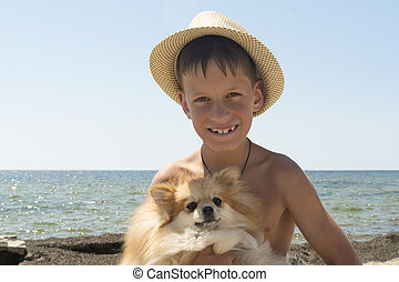 Happy 8 year old boy hugging his dog Pomeranian Shpitz at the seashore against a blue sky.