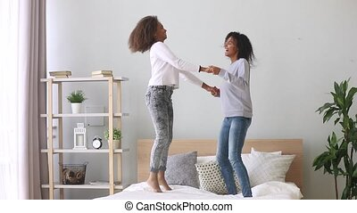 Happy active african mom with teen daughter jumping on bed