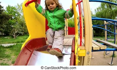 Happy Active Little Boy Sliding Down At Playground