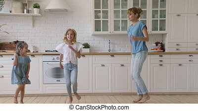 Happy active mom and two children dancing together in kitchen