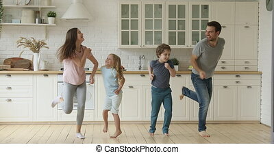 Happy active parents and cute children jumping together in kitchen