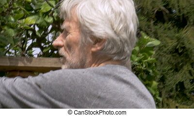 Happy active retired senior man rebuilding a broken fence in...