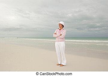 Happy active retirement woman isolated beach