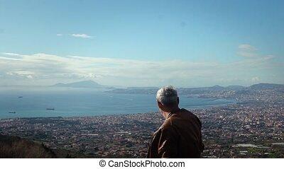 Happy active senior Caucasian male tourist enjoying epic view panorama of sunny Naples from Vesuvius, Italy slow motion.