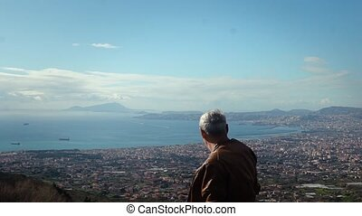 Happy active senior Caucasian male tourist enjoying epic view panorama of sunny Naples from Vesuvius, Italy slow motion. Excited older tourist man enjoying active retirement on vacation in Europe.