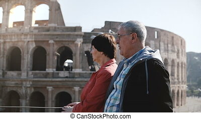 Happy active senior Caucasian tourist couple enjoying the view of famous Coliseum together during trip to Rome, Italy.