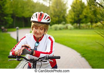 Happy active senior woman on bike