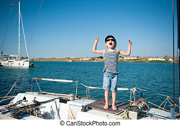 happy active small caucasian kid in sailor hat shouting with joy on white yacht board during summer travel vacation