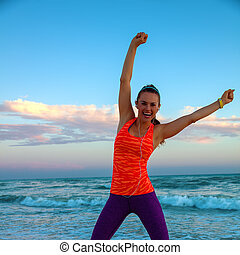 happy active woman on seashore at sunset rejoicing