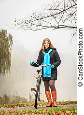 Happy active woman with bike in autumn park.