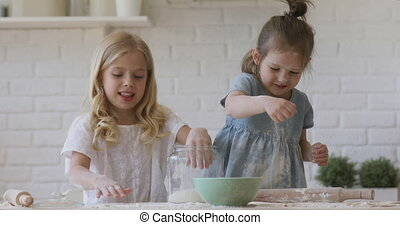 Happy adorable kids sisters enjoy cooking together preparing dough, two cute funny children girls playing with flour sugar having fun in kitchen, happy preschool siblings help baking laughing at home