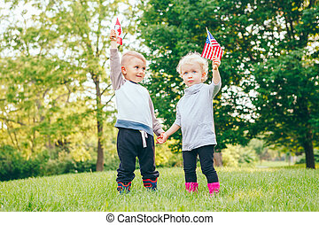 Caucasian girl and boy smiling laughing holding hands and waving American and Canadian flags
