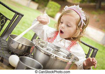 Happy Adorable Little Girl Playing Chef Cooking in Her Pink Outfit.