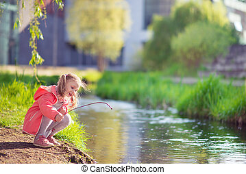 Happy adorable little girl playing near pond in sunny day