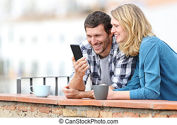 Happy adult couple checking smart phone in a balcony