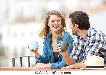 Happy adult couple talking and drinking coffee in a balcony