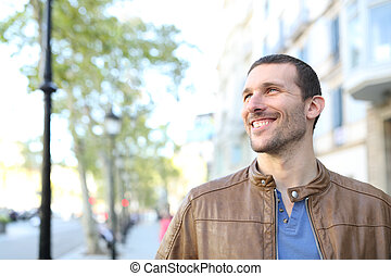 Happy adult handsome man looking at side in the street