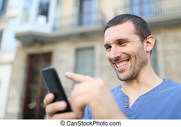 Happy adult man browsing phone content in the street