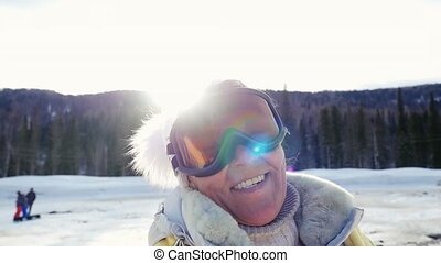 Happy adult woman smiles against mountains in winter in slowmotion on the sun background. 1920x1080