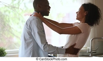 Happy affectionate african american young couple bonding...