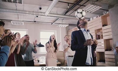 Happy African American boss juggles ball on head....