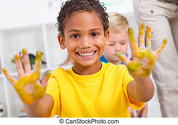 happy african american boy with hand paint in classroom
