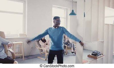 Happy African American businessman celebrating promotion with funny dance walk. Successful boss in modern office 4K.