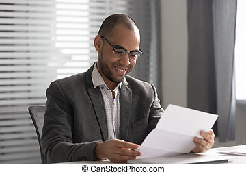 Happy African American businessman reading document, receiving good news