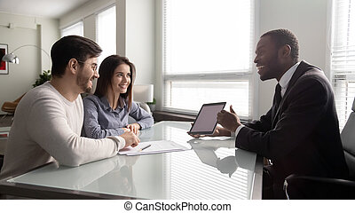 Happy african american businessman showing mockup on tablet.
