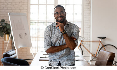 Happy african american businessman standing in modern office, business portrait