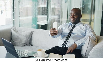 Happy African American businessman taking a selfie on his smartphone and showing a thumb up gesture while drinking coffee in modern cafe.