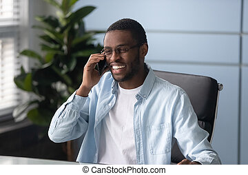 Happy african american businessman wearing glasses talking on phone.