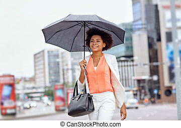 happy african american businesswoman with umbrella
