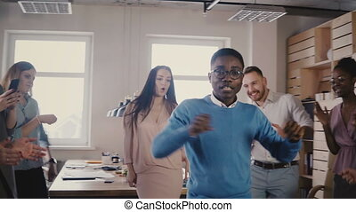 Happy African American CEO dancing with friends at casual...