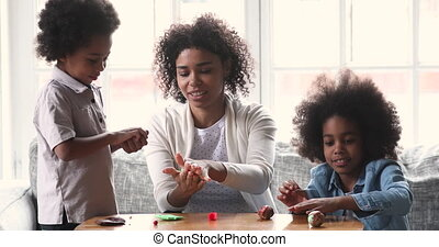 Happy african american children making shapes with plasticine with mom.