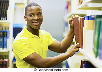 african american college boy pulling library book