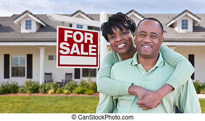 Happy African American Couple In Front of Beautiful House and For Sale Real Estate Sign.