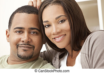 Happy African American Couple Sitting At Home - A happy...