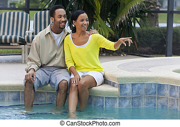 Happy African American Couple Sitting By Swimming Pool Pointing