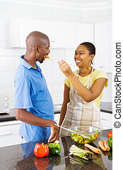 couple tasting food - happy african american couple tasting...