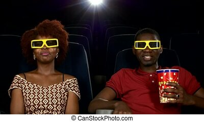 Happy African American couple, watching movie In theatre, Close up. 3D stereo glasses