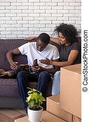 Happy African American couple with dog just moving in new house