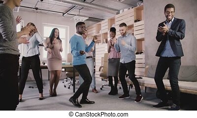 Happy African American employee dancing with colleagues at office party, celebrating business achievement slow motion.