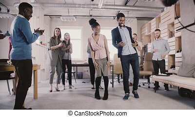Happy African American employees doing fun ethnic dance at office party, celebrating business achievement slow motion.