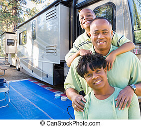 Happy African American Family In Front of Their Beautiful RV At The Campground.