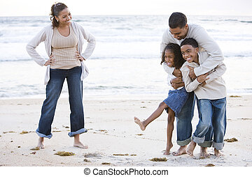 Happy African-American family laughing on beach