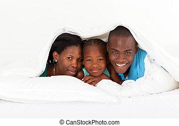 African American family lying under duvet